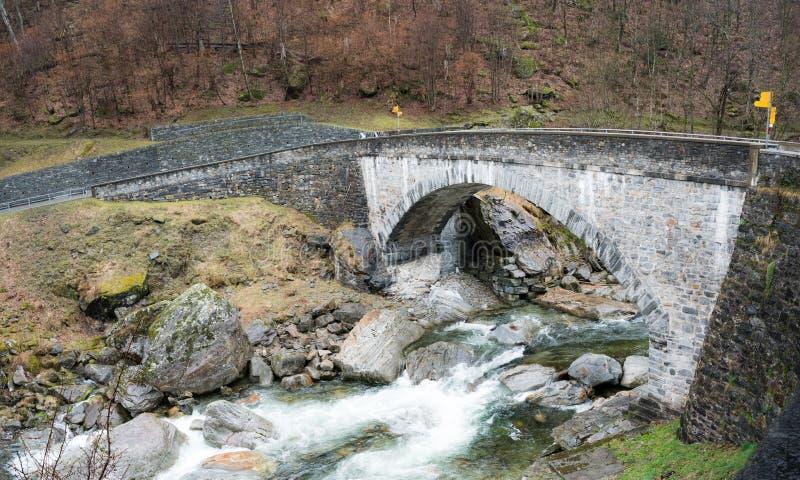 穿过有足迹标志和供徒步旅行的小道的老石桥梁一条狂放的河在双方 免版税库存照片