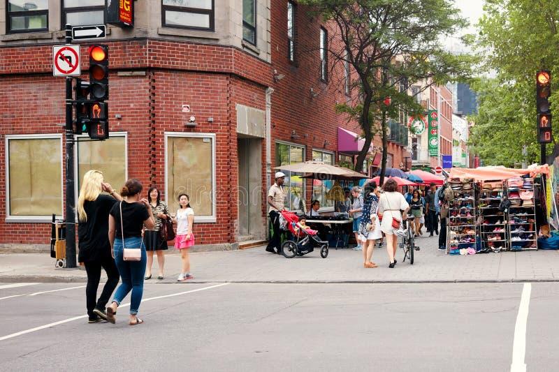 穿过街道和购物在市场上的中国,美国黑人和白种人人民在唐人街在蒙特利尔,魁北克, 免版税库存图片