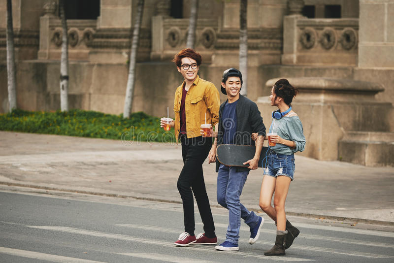 穿过街道的时髦的亚裔朋友 库存图片