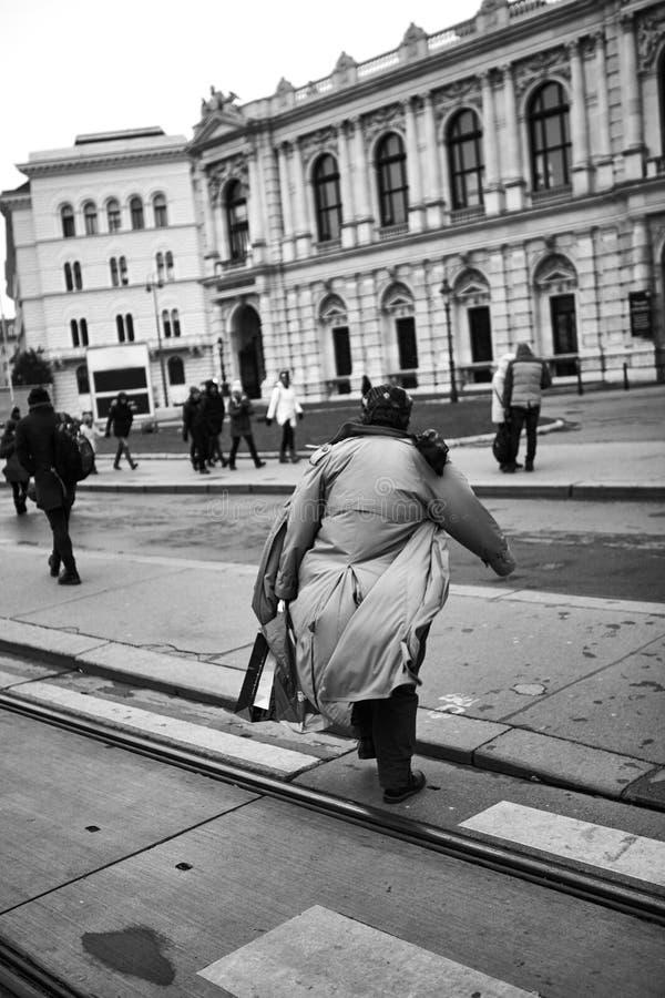 穿过路的一件皮革外套和太阳镜的人在白天 黑色白色 库存图片