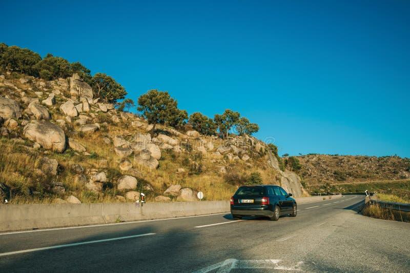 穿过路的汽车在日落的多小山风景 库存图片