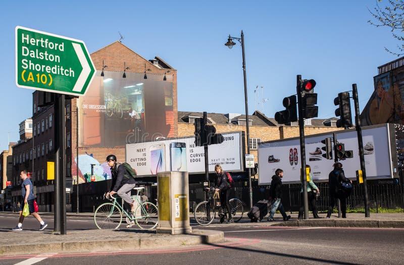 穿过路的行家骑自行车者在繁忙的交叉路 免版税库存照片