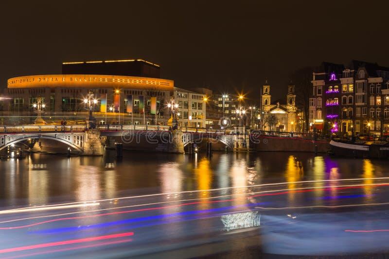 穿过Amstel河的Stopera和蓝色桥梁在t的晚上 库存照片