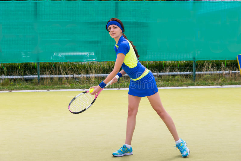 穿运动服的年轻女性网球员打网球o 库存照片