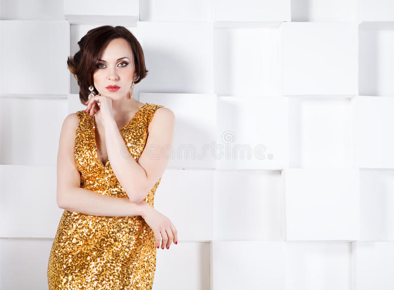 穿金黄光亮的礼服的超级明星妇女 库存照片