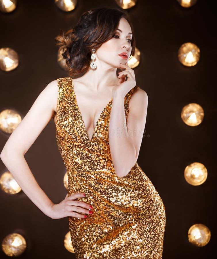 穿金黄光亮的礼服的超级明星妇女 免版税图库摄影