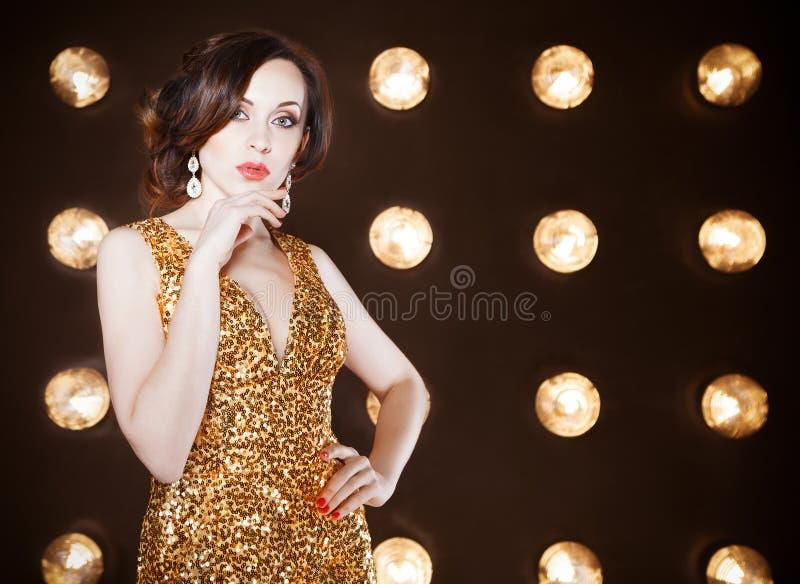 穿金黄光亮的礼服的超级明星妇女 免版税库存图片