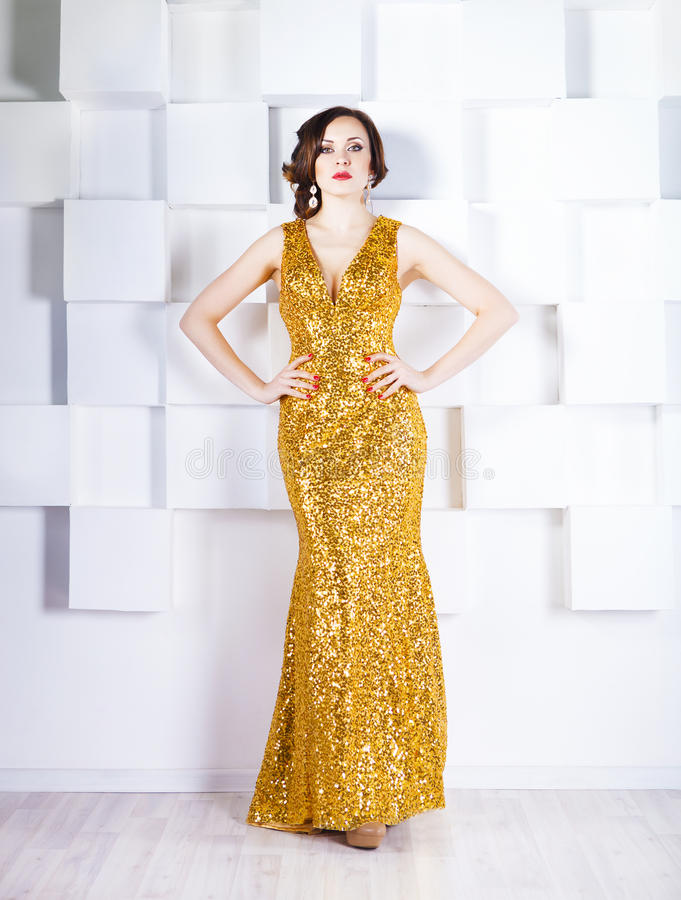 穿金黄光亮的礼服的超级明星妇女 图库摄影
