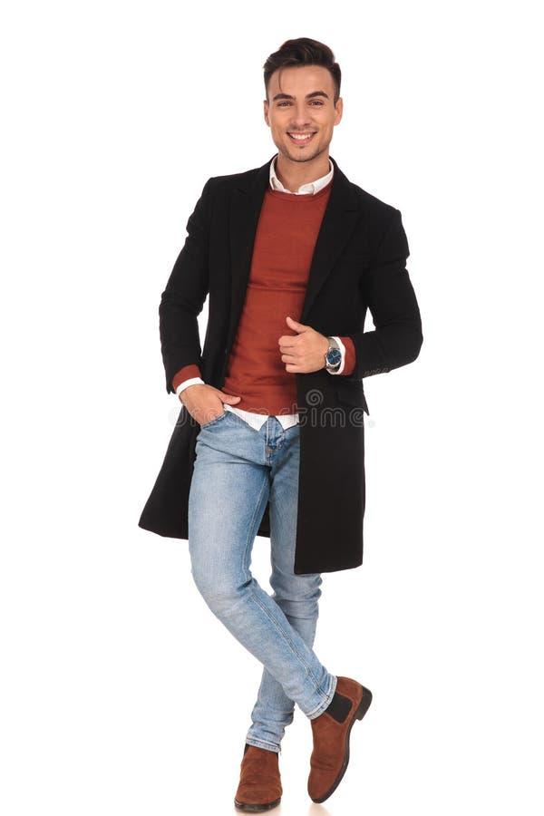 穿长的外套的笑的年轻人 库存照片