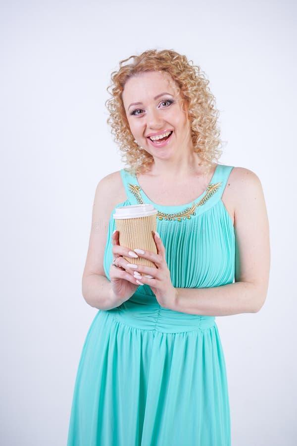 穿长的蓝色夏天礼服的俏丽的白肤金发的白种人妇女拿着纸咖啡和享有在白色演播室backgroun的生活 免版税库存照片