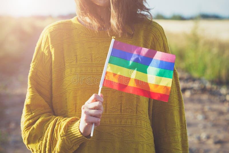 穿黄色毛线衣的年轻女人拿着lgbt彩虹旗子外面,同性恋人,自由,爱, 库存照片