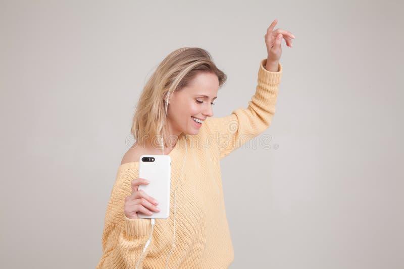 穿黄色毛线衣的年轻白肤金发的妇女召回好的记忆作为与lisening音乐的耳机的跳舞,拿着智能手机和 图库摄影