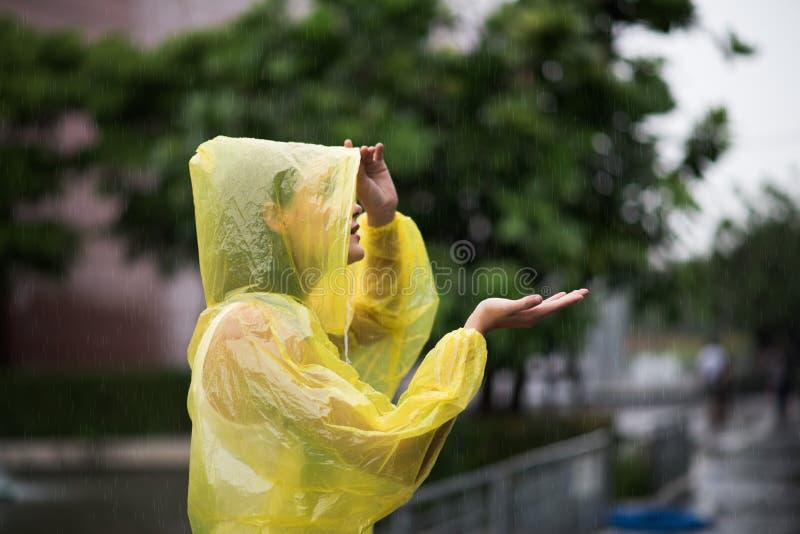 穿黄色雨衣的妇女,当下雨在雨季时 免版税库存图片