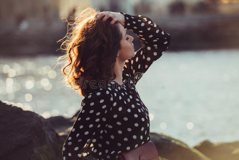 穿黑圆点礼服的美丽的女孩享用在海洋海滩的夏天太阳在日落时间 免版税库存照片