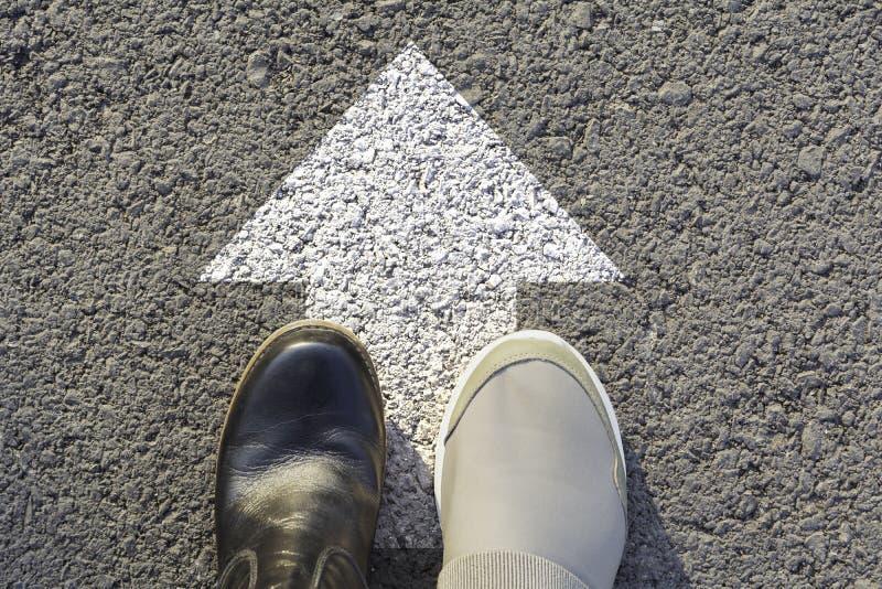 穿黑白鞋子的人顶视图选择方式标记用白色箭头 选择正确的道路概念 库存图片
