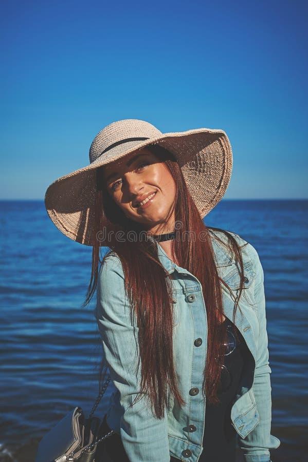 穿黑礼服和牛仔裤夹克的红头发人女孩 背景剪报帽子查出的路径秸杆白色 站立在沙子的妇女 减速火箭的被定调子的图象 免版税库存照片