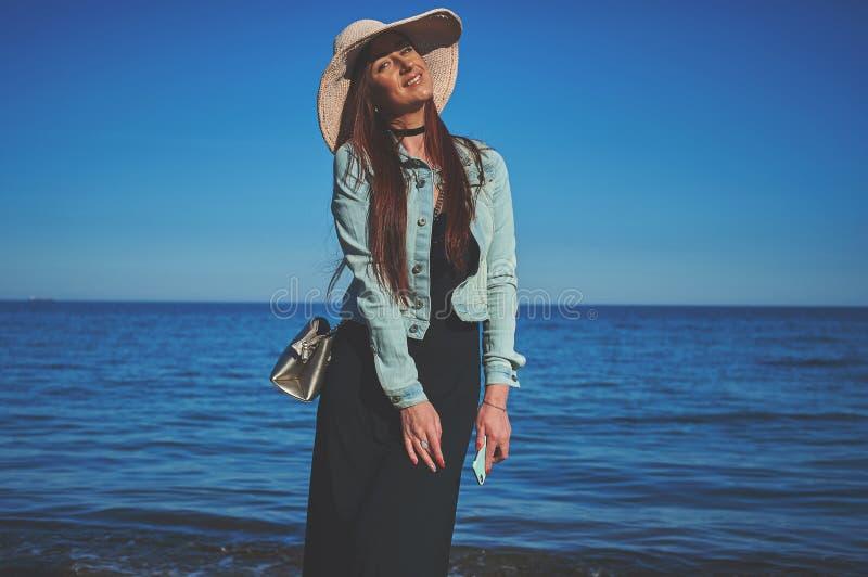 穿黑礼服和牛仔裤夹克的红头发人女孩 背景剪报帽子查出的路径秸杆白色 Ho 图库摄影