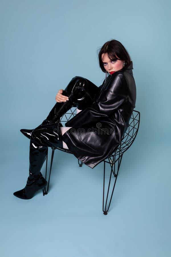 穿黑礼服和黑起动与黑短发的哥特式女孩 图库摄影