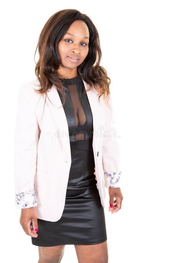 穿黑礼服桃红色夹克性感的女用贴身内衣裤的迷人的妇女非裔美国人秀丽画象站立被隔绝的白色 库存照片