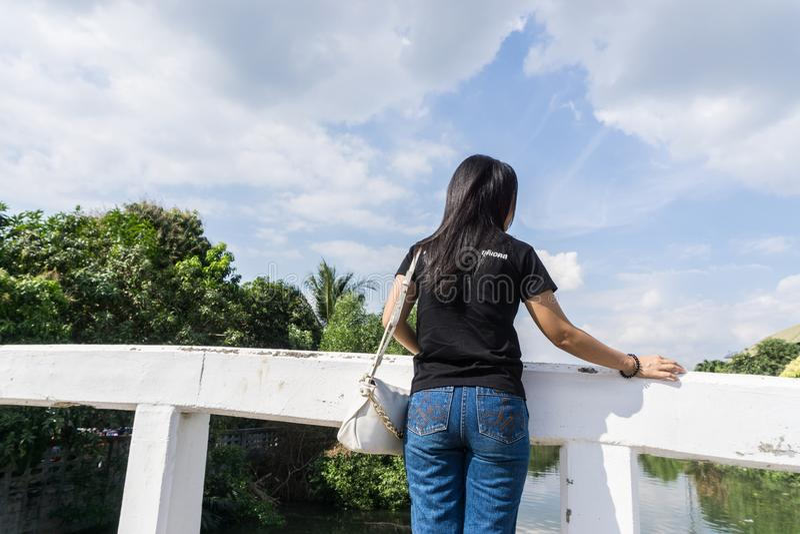 穿黑衬衣的后面观点的年轻妇女站立在老桥梁和神色在天空 图库摄影