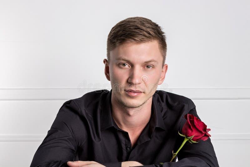 穿黑衬衣的帅哥拿着玫瑰和准备好浪漫日期 库存照片