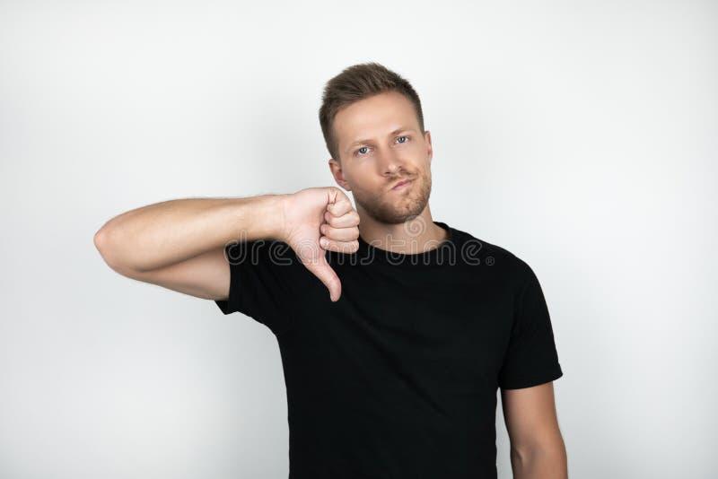 穿黑T恤杉的英俊的年轻人显示反感有消极表示被隔绝的白色背景 免版税库存照片