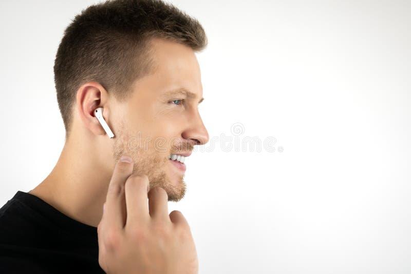 穿黑T恤杉的英俊的年轻微笑的人有通话使用在被隔绝的白色的无线耳机 免版税库存图片