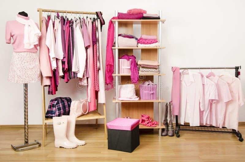 穿戴与桃红色衣裳的壁橱在挂衣架安排了,并且架子,在时装模特装备。 图库摄影