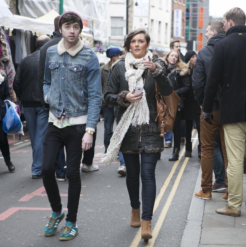 穿戴了走在砖车道,街道的行家女孩和男孩在凉快的伦敦人样式受欢迎在年轻时髦人民中 图库摄影