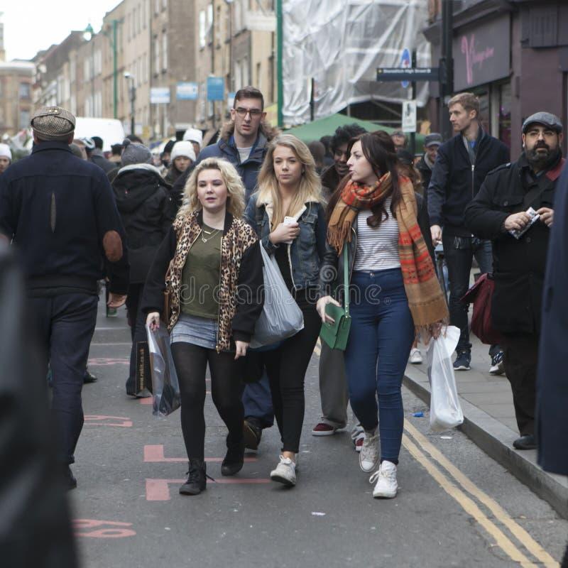 穿戴了走在砖车道,街道的行家女孩在凉快的伦敦人样式受欢迎在年轻时髦人民中 库存照片