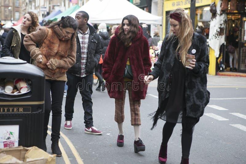 穿戴了走在砖车道,街道的行家女孩在凉快的伦敦人样式受欢迎在年轻时髦人民中 免版税库存图片