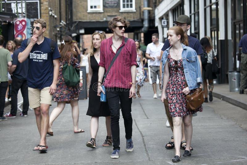 穿戴了走在砖车道,街道的行家男人和妇女在凉快的伦敦人样式受欢迎在年轻时髦人民中 免版税库存照片