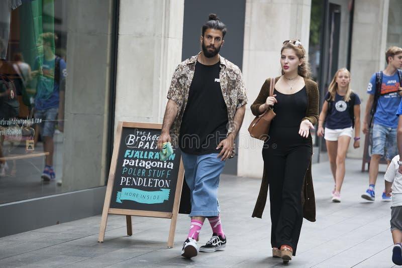 穿戴了走在Bric的两个行家女孩在凉快的伦敦人样式 库存照片