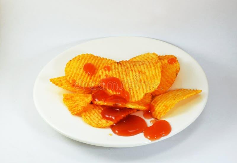 穿戴在盘的土豆片番茄酱 免版税库存照片