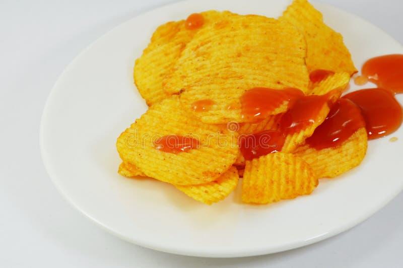 穿戴在盘的土豆片番茄酱 库存图片