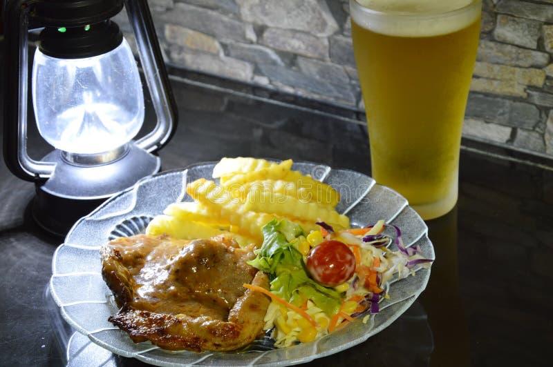穿戴小汤调味汁和啤酒的猪肉牛排 免版税库存照片