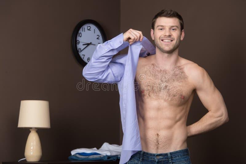 穿他新的衬衣。 库存照片