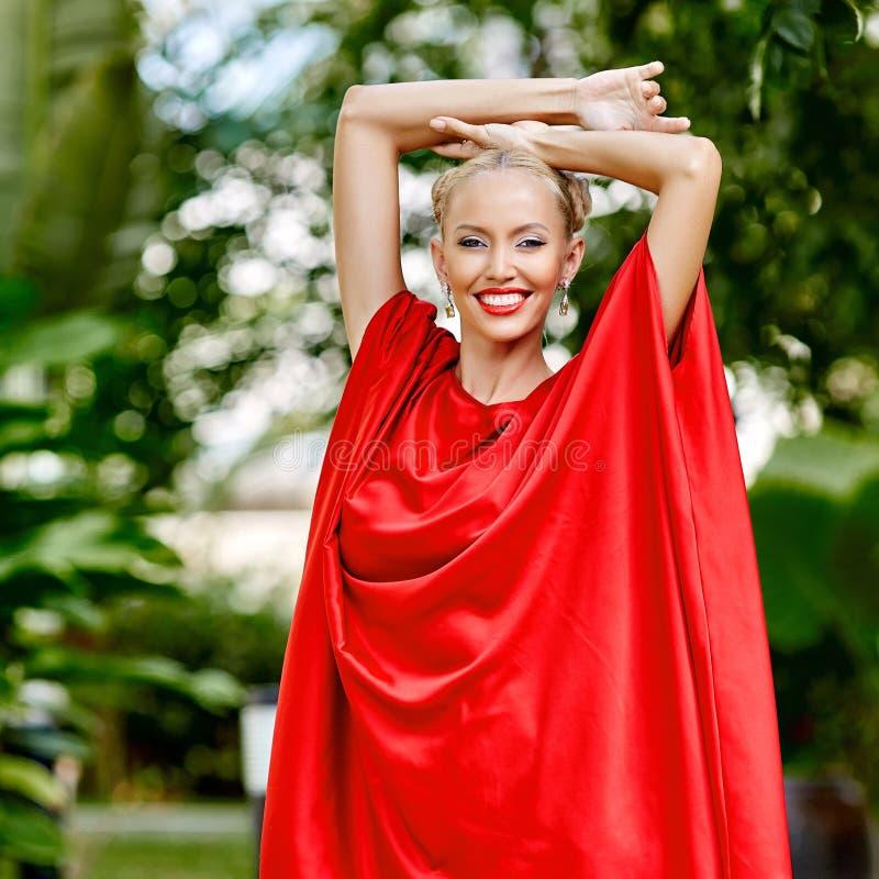 穿戴方式壮观的照片红色工作室妇女年轻人 室外p 库存照片