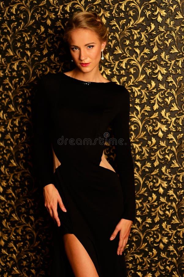 穿黑晚礼服的美丽的女孩 免版税图库摄影
