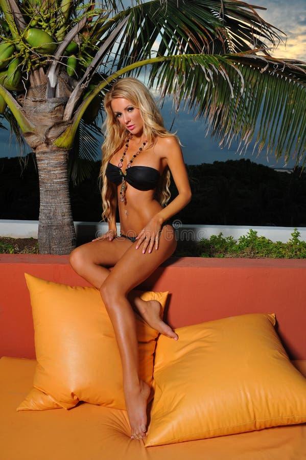 穿黑比基尼泳装的白肤金发的模型 库存图片