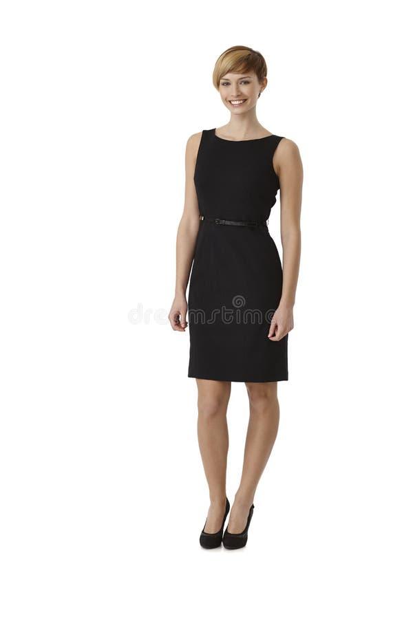 穿黑燕尾服的可爱的妇女 免版税库存照片