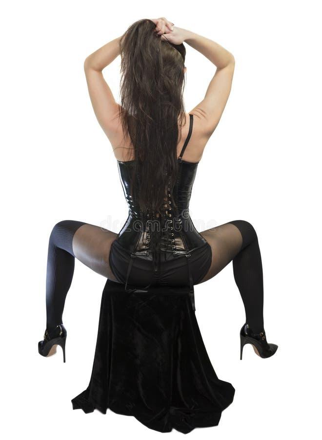 穿黑皮革束腰的坐的女孩 图库摄影