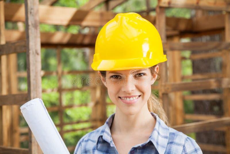 穿黄色安全帽的确信的女性建筑师 免版税库存照片