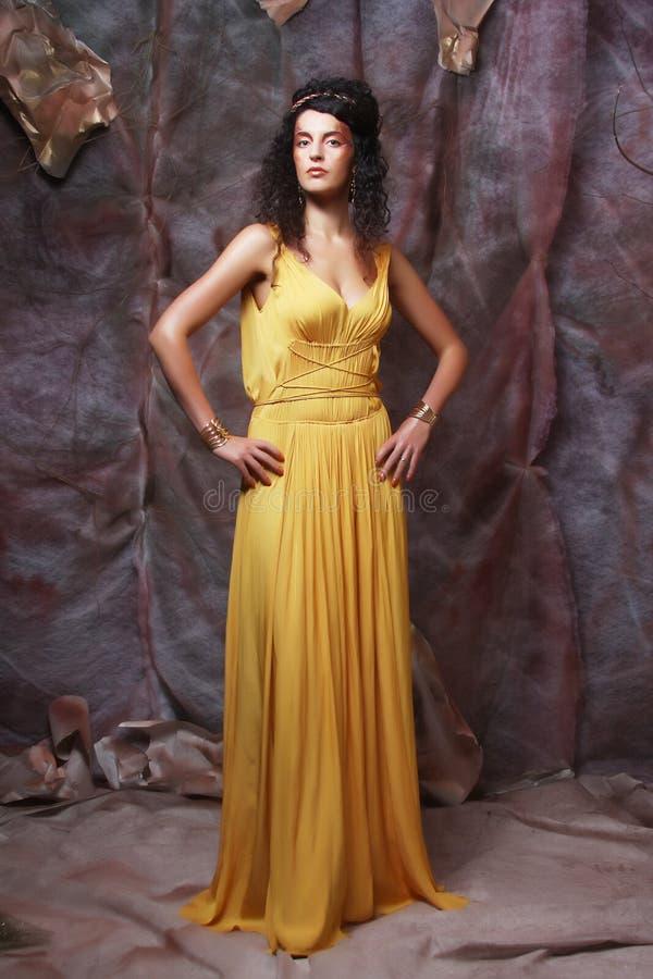 穿黄色晚礼服的深色的妇女 库存图片