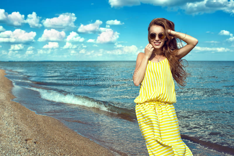 穿黄色镶边宽松的夏天最大的礼服的美丽的年轻微笑的妇女在海边 免版税库存照片