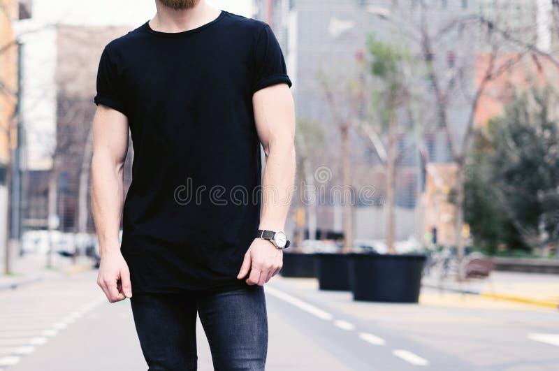 穿黑T恤杉和牛仔裤的特写镜头观点的年轻肌肉人摆在现代城市的街道上 蠢材 免版税库存照片