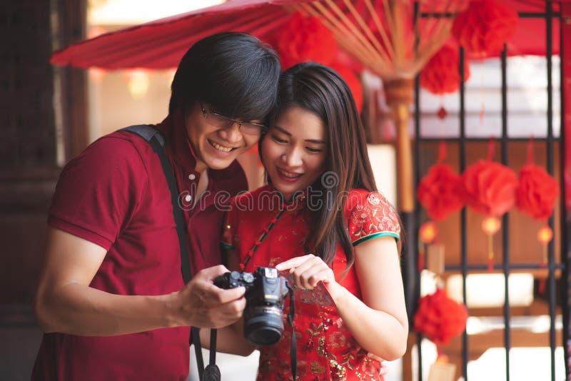 穿Cheongsam传统红色礼服和T恤杉和看在旅行旅行的照相机的愉快的亚洲中国夫妇在中国新 免版税库存图片