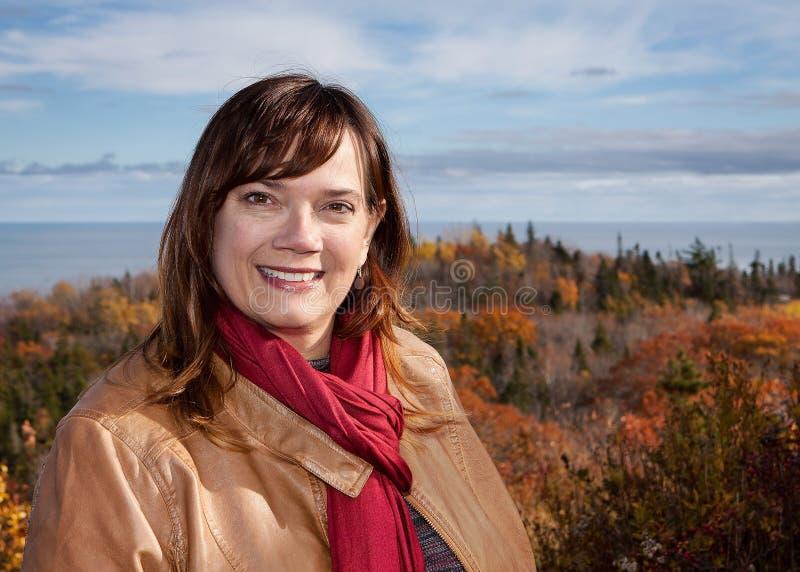 穿Tan皮夹克和红色围巾有风景秋天颜色和海洋背景的一名白种人妇女的画象 库存图片