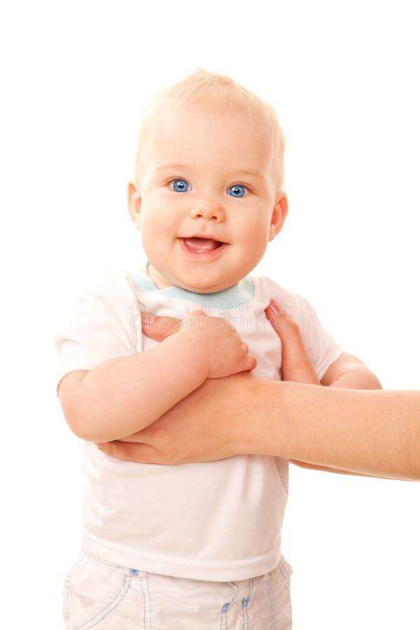 突出与母亲的胳膊的愉快的蓝眼睛的婴孩 免版税库存图片