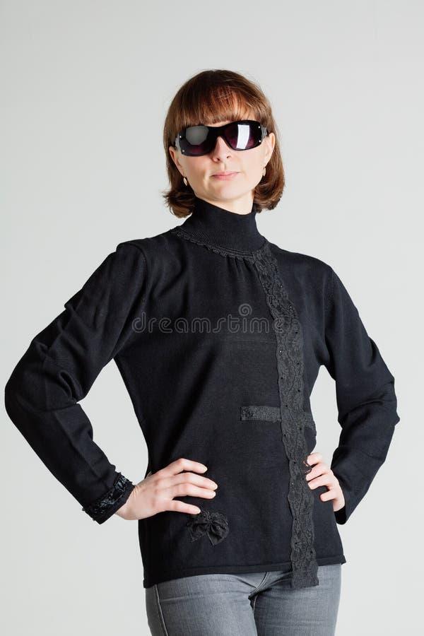 突出与胳膊的太阳镜的妇女两手插腰 免版税库存图片
